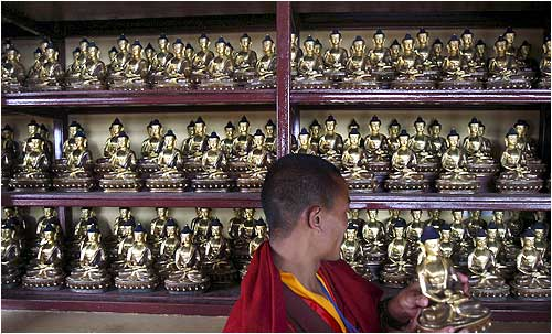 A monk adjusts Buddha statuettes at a monastery in Kathmandu