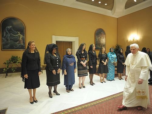 The Pope walks past the First Ladies