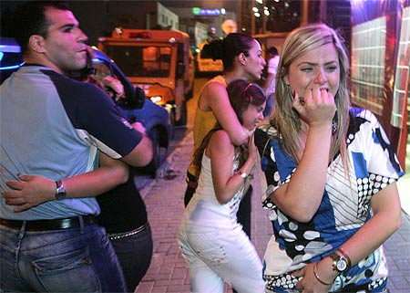 Local residents react near the scene of a rocket attack in the southern Israeli town of Sderot