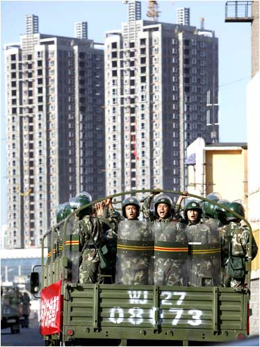 Chinese troops shout slogans as they ride a truck on the main street of Urumqi