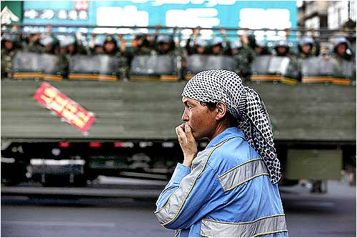 An ethnic Uighur woman stands on the side of the road as Chinese troops ride on a truck