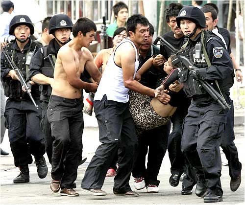 Policemen carry a woman who had fainted on a street in Urumqi