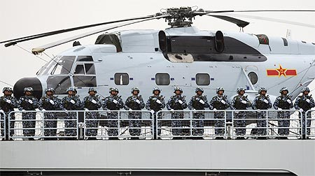 Chinese Marines stand at attention on a warship while taking part in an international fleet review to celebrate the 60th anniversary of the founding of the People's Liberation Army Navy in Qingdao, Shandong province