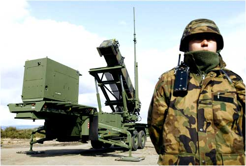 A soldier stands next to a Japanese Self-Defence Force Patriot Advanced Capability-3 (PAC-3) missile unit