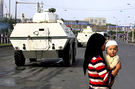 An ethnic Uighur woman carries her child across the road as Chinese armoured personnel carriers drive past