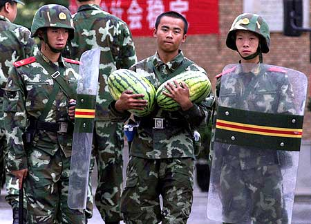 A Chinese soldier carries two watermelons as he walks past two fellow soldiers in riot gear guarding a mosque in the city of Urumqi