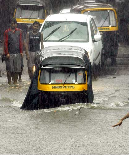 An autorickshaw moves through a flooded road