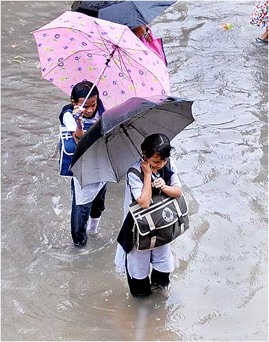 School kids walk through a flooded street