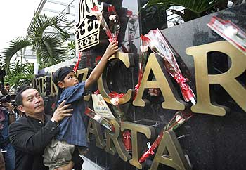 A boy places a flower in front of the Ritz-Carlton hotel in memory of those killed by a bomb blast, in Jakarta