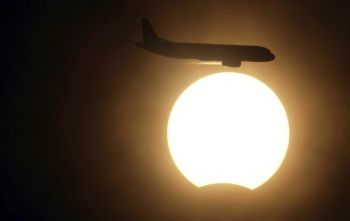 An aircraft manoeuvring during the solar eclipse in New Delhi