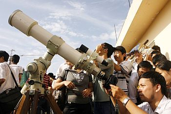 A scientist takes a photo of the eclipse through a telescope