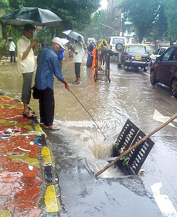 Municipal workers clear a flooded drain