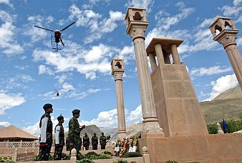 Indian army helicopters fly past as a senior army officer pays homage at war memorial during Vijay Diwas in Drass