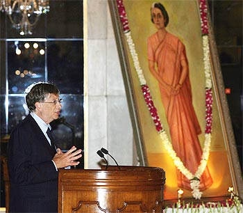 Bill Gates speaks beside a portrait of India's former prime minister Indira Gandhi during the conferment ceremony