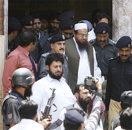 Mohammad Saeed (in a white cap), founder of the Lashkar-e-Tayiba, leaves a Lahore court.