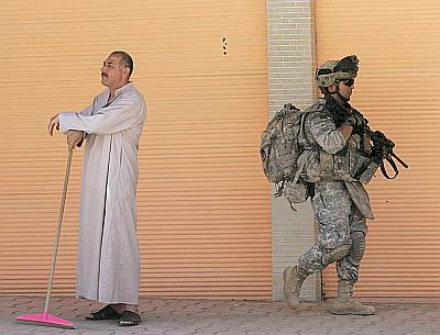 A US soldier walks past a resident during a patrol in Samarra