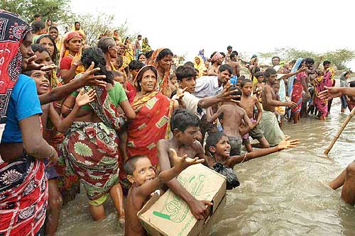 Homeless villagers reach out for aid material in Khulna, Sunderbans