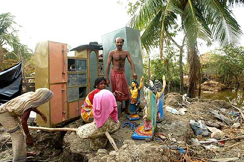 Villagers sit amidst the remains of their houses