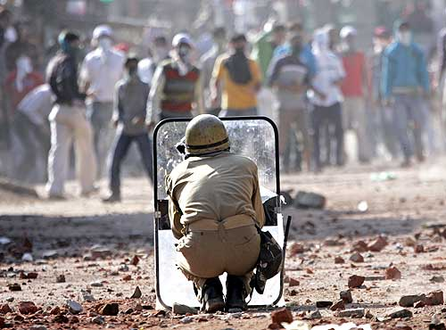 A policeman faces protesters in Srinagar
