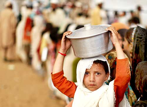 An internally displaced girl, fleeing military operations in the Swat valley region, holds a pot over her head while standing in line for curry and bread at the UNHCR camp