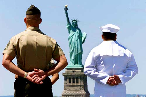 A US Navy sailor stands with a US Marine aboard the USS Iwo Jima as the ship passes the Statue of Liberty in New York Harbour
