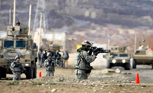 US soldiers keeps watch at the scene of a suicide car bomb attack in Parwan province