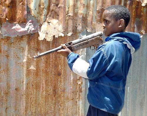 A boy plays with a gun at a village in Somalia's capital Mogadishu
