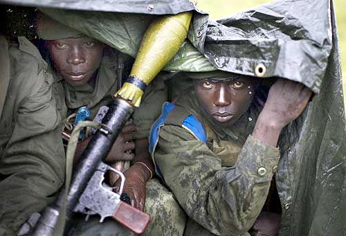 Congolese government soldiers sit in the rain at the frontline near Kibati, north of Goma in eastern Congo