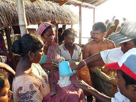 A victim in Gosaba gets a mug of flattened rice