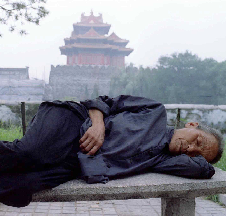 An elderly Chinese woman naps on a park bench near the Forbidden City in China