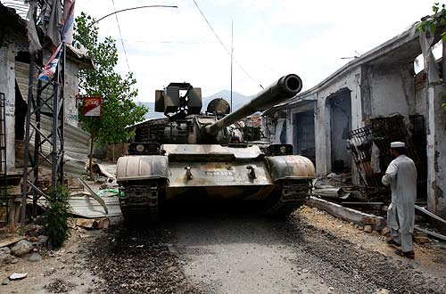 A tank passes through a street past damaged shops at Maidan at Lower Dir district in the Swat region on June 13