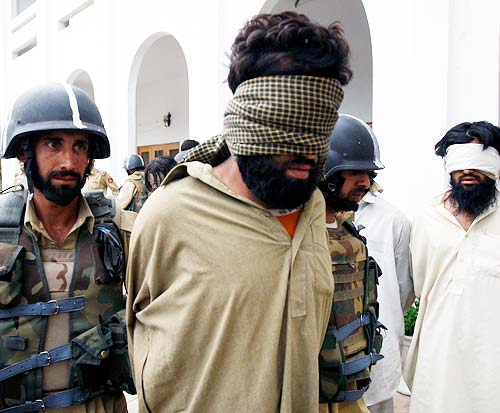 Soldiers take away a blindfolded suspected militant after showing him to the media in Lower Dir district in Swat region