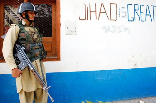 Security personnel stand outside a building at Lower Dir district, in the Swat region