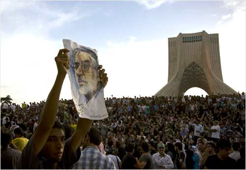 A demonstrator holds up a picture of Mousavi during the rally