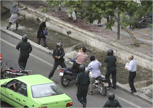 A riot policeman hits a motorcyclist with a baton during the protest