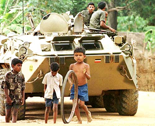 Tamil children in a refugee camp play with a bicycle rim in front of a Sri Lankan battle tank