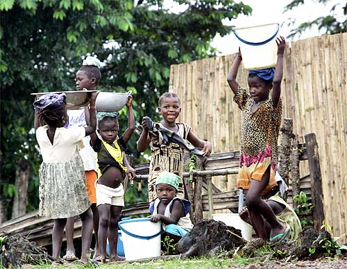 Liberian refugees gather around a water well in a refugee camp in Tobonda, near Kenema in Sierra Leone