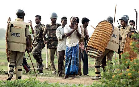 A villager begs a policeman to spare him after his arrest near Lalgarh