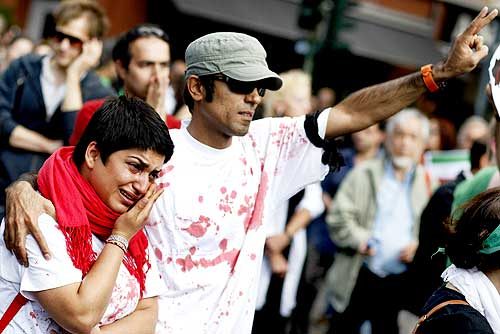 A protester cries as another flashes a victory sign during a demonstration in support of the Iranian opposition