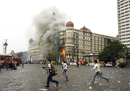 Photographers run past the burning Taj Mahal hotel in Mumbai, November 29, 2008