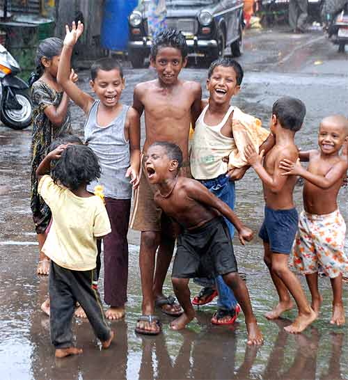 Children dance in the street as the first monsoon showers hit Mumbai