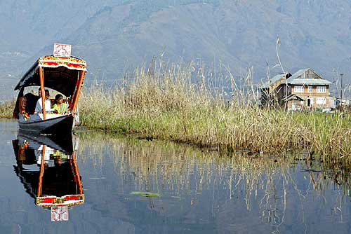 Tourists take a boat ride on the Dal Lake