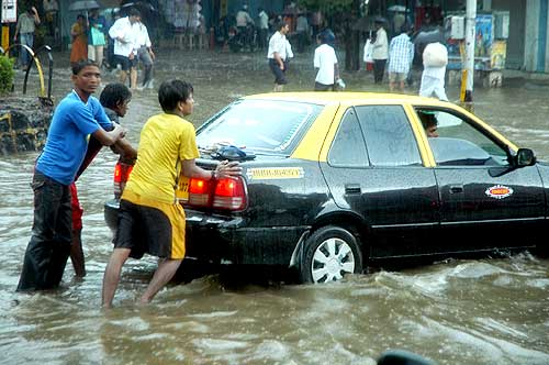People push a cab stranded in rain-water