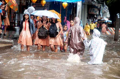 School children make their way through the flooded pavement