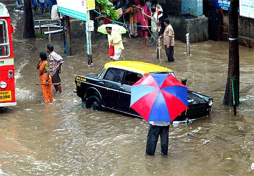 A taxi stranded at a flooded road-side