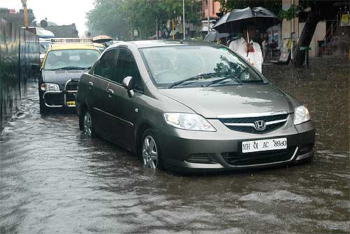 Vehicles navigate through a flooded street