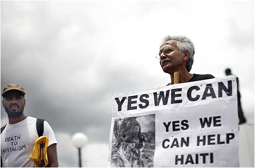 A demonstrator seeks more aid for Haiti outside the