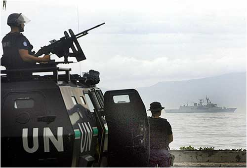 Australian navy ship HMAS Perth is seen as Portuguese policemen patrol near the house of rebel leader Alfredo Reinado