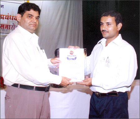 Bablu Kumar Deepak (right) receives an award from the divisional railways manager.