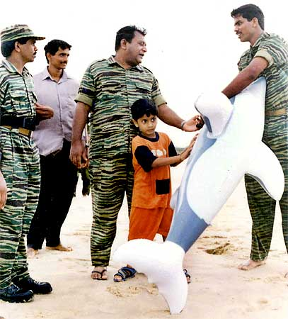 An undated photograph supplied by the Sri Lankan Ministry of Defence shows LTTE leader Prabhakaran playing with his son Balachandran as soldiers from the LTTE watch